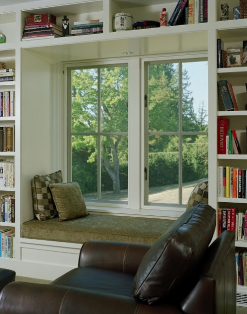 a window sill reading seat with built-in bookshelves and a comfortable daybed is a perfect space to have a rest