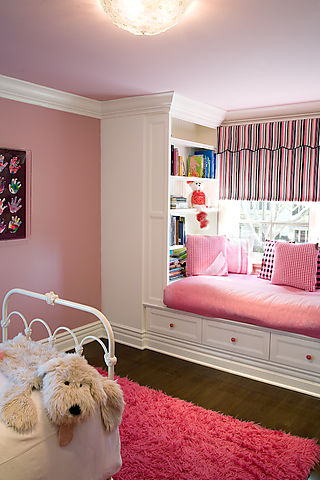 a cozy built in window seat in pink, with lots of pillows and large built in bookshelves on each side