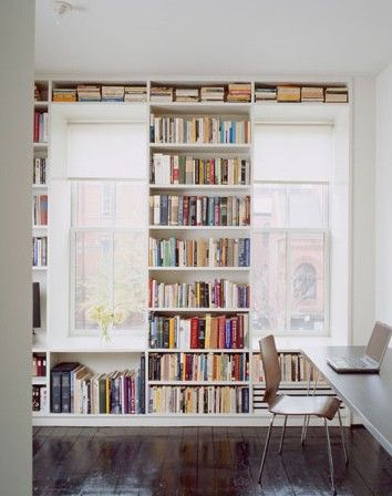 a bookshelf placed between the windows and under the windowsills that also forms natural seats for reading here