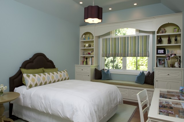 a cozy window seat with bright pillows and shelves on each side looks bright, fun and cool