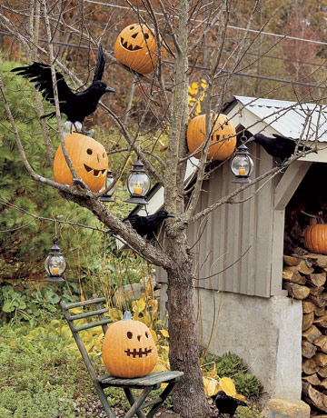 a tree with blackbirds, pumpkin lanterns and candel lanterns hanging on the tree is a chic Halloween decoration