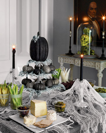a silver vintage stand with black and grey pumpkins, black candles, spiderweb and spiders for creating an elegant Halloween tablescape