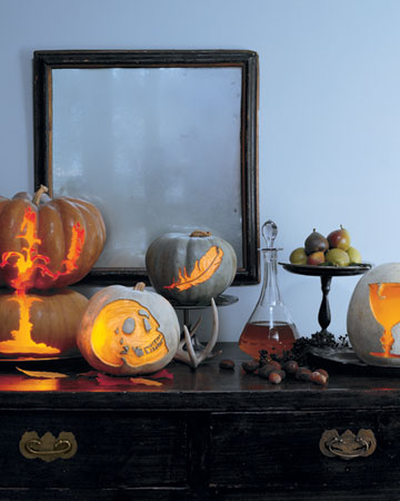 a scary Halloween console table with pretty carved pumpkin lanterns, poison in a bottle and some fruit is elegant