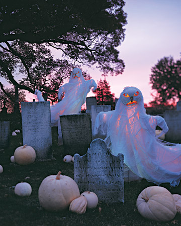 a graveyard with pumpkins and ghosts is a bold scary backyard decoration you may create for Halloween