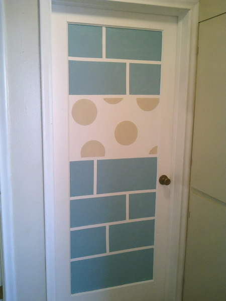 a white door stenciled with tile-like patterns and polka dots to make it whimsy and bright