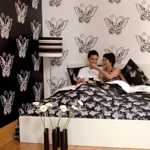 monochromatic butterfly print wallpaper and matching bedding for a whimsical bedroom look yet a classic color scheme