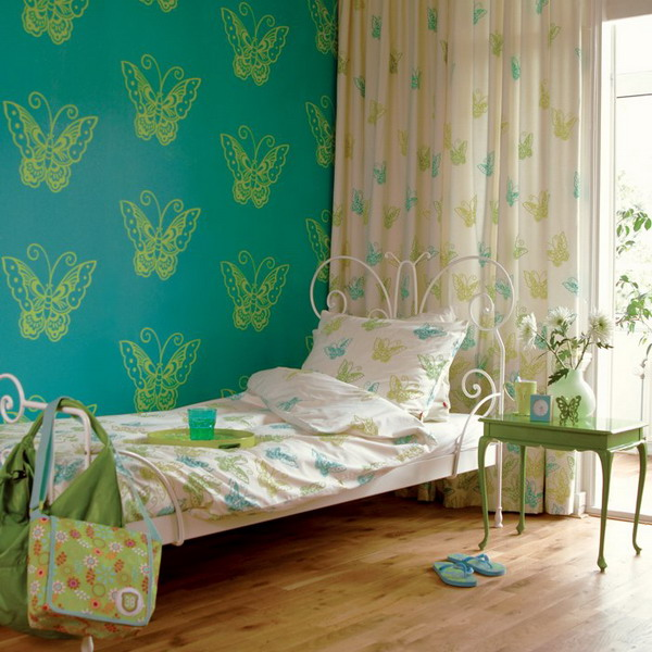 a turquoise wall with butterfly printing, printed bedding and curtains make the space look very quirky