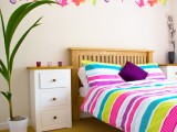 colorful butterfly wall decals and matching bright striped bedding for a bold and fun bedroom look