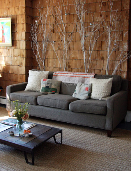 whitewashed branches placed behind the sofa to add a natural feel to the living room