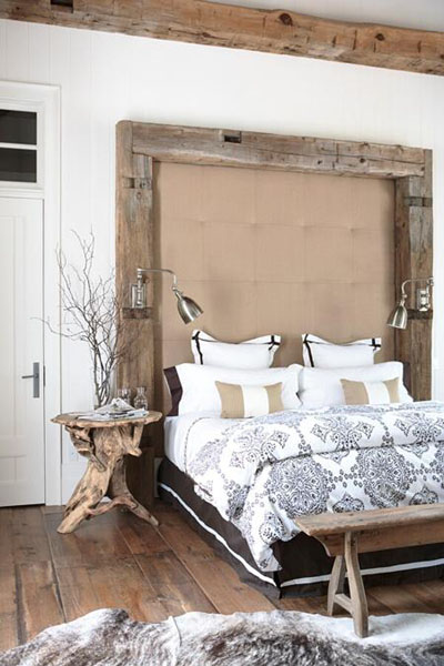 a coffee table made of driftwood and some branches in a clear vase will make your bedroom feel super natural and coastal