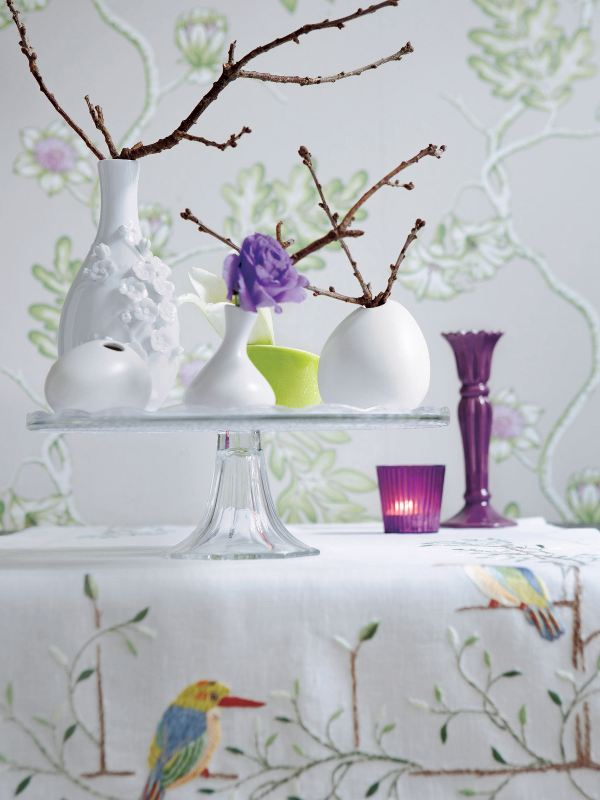 a glass stand with an arrangement of vases and lots of natural branches can work as a spring centerpiece