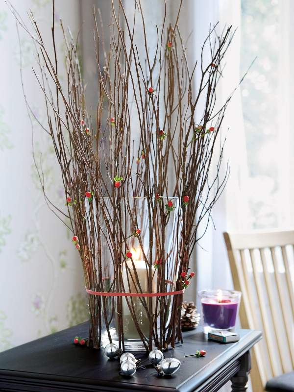 a glass candleholder wrapped with branches with berries is a cool natural idea and an easy DIY