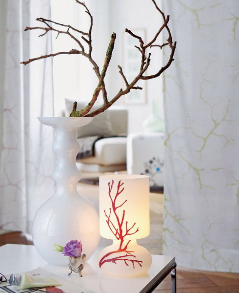 a white vase with spectacular tree branches covered with moss is a cool arrangement with a slight woodland feel