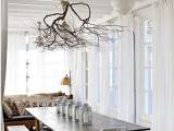 attach tree branches to the ceiling railing, which holds your lamps, to make the space feel more natural