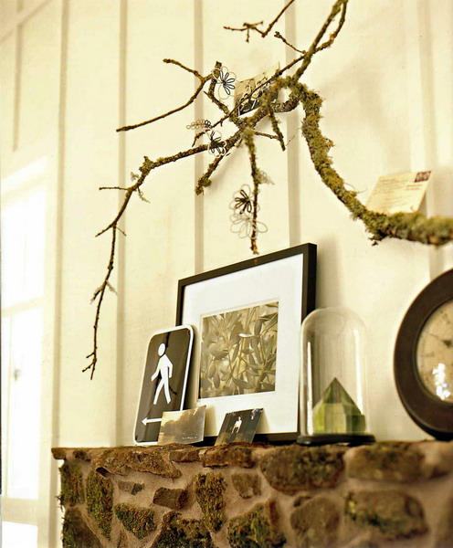 moss covered branches attached to the wall and yarn blooms will make your mantel more eye-catching