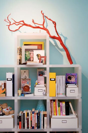 a branch painted red and placed on a neutral shelf works as a pretty decoration you can rock anytime