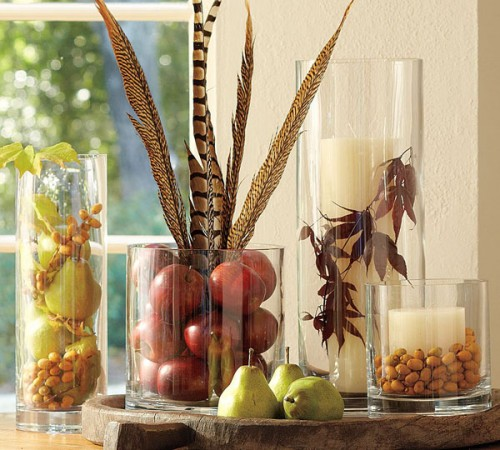 a cool fall centerpiece of glasses with faux fruit, feathers, dried leaves, nuts and acorns is very natural