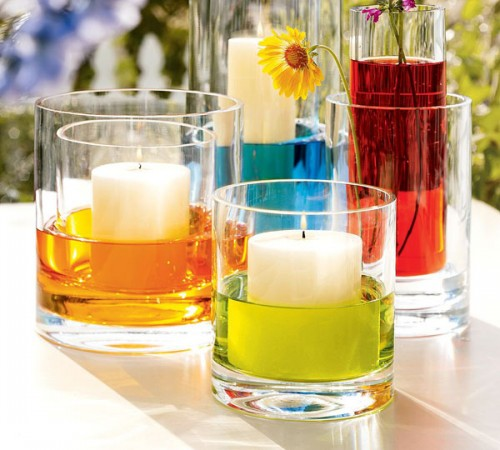 glasses with colorful water and pillar candles placed into them in other glasses look fun and bold