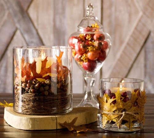 glasses with nuts, dried leaves, cranberries and candles and a jar with faux pomegranates is a cool fall centerpiece or decoration