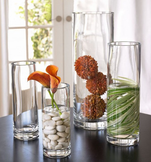 large and tall glass vases with pebbles, leaves and dried blooms create a cool chic fall arrangement