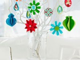 Felt ornaments looks great dangling on branches in a vase. Spray paint these branches with white paint to highlight the design of these ornaments. (via familycircle)