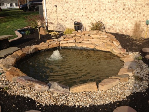 7 diy natural rock ponds to transform your backyard for Stone koi pond