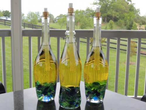 wine bottles tiki torches with crafting pebbles (via armchairsommelier)