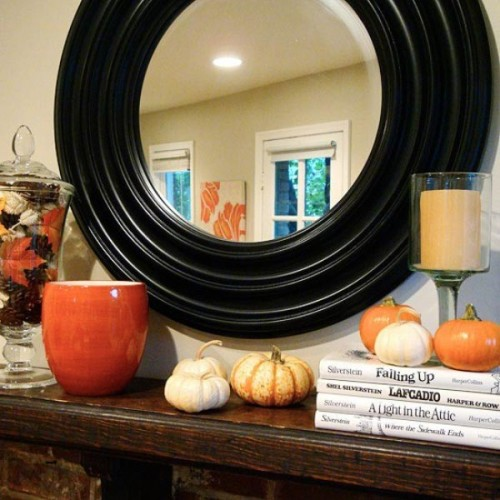 This simple display features small pumpkins along with a vase filled wth autumnal leaves and pinecones.