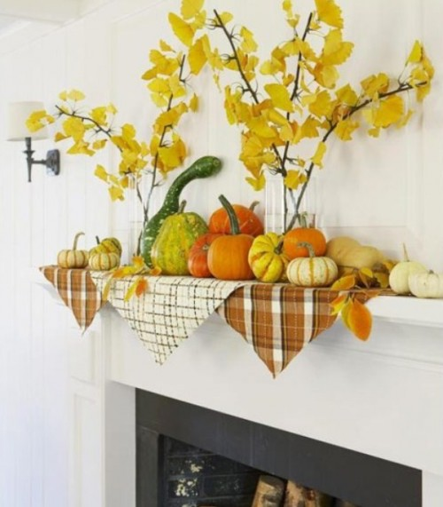 An assortment of gourds and and pumpkins is perfect idea for a simple mantel display. Several branches with leaves provide extra texture to it.