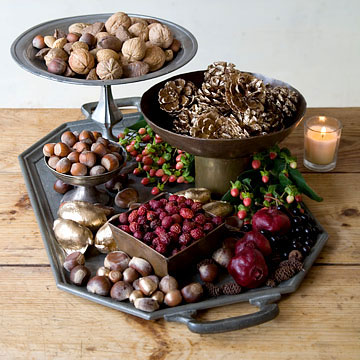 a multi-level fall display with nuts, pinecones, gilded pinecones, berries, candles and fruits