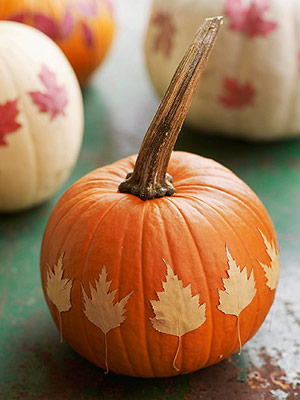 a pumpkin with dried fall leaves attached to it is a nice and bold decoration for the fall