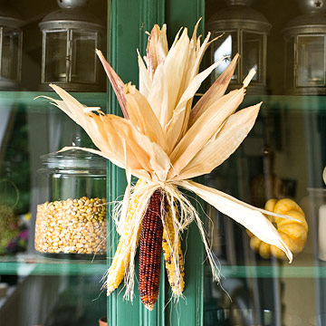 dried corn cobs and husks accent a cabinet for a fall touch, you may also hang them on doors or your front door