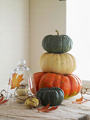 stacked pumpkins and fall leaves all around is a cool fall centerpiece with a strong natural feel