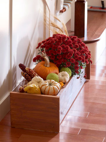 a box with pumpkins, dried corn and fall blooms is a bold rustic decoration you can create for the fall