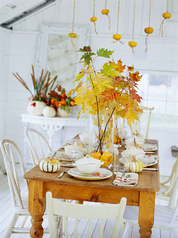 a glass vase with pumpkins and branches with bold leaves is a cool and all-natural modern fall centerpiece