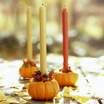 fall colored candles in pumpkins and with pinecones are a perfect craft for the fall