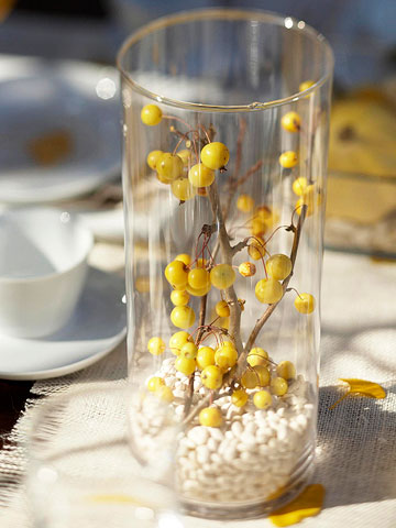 a tall glass vase with white pebbles and branches with berries is a cool fall decoration or centerpiece with a touch of color
