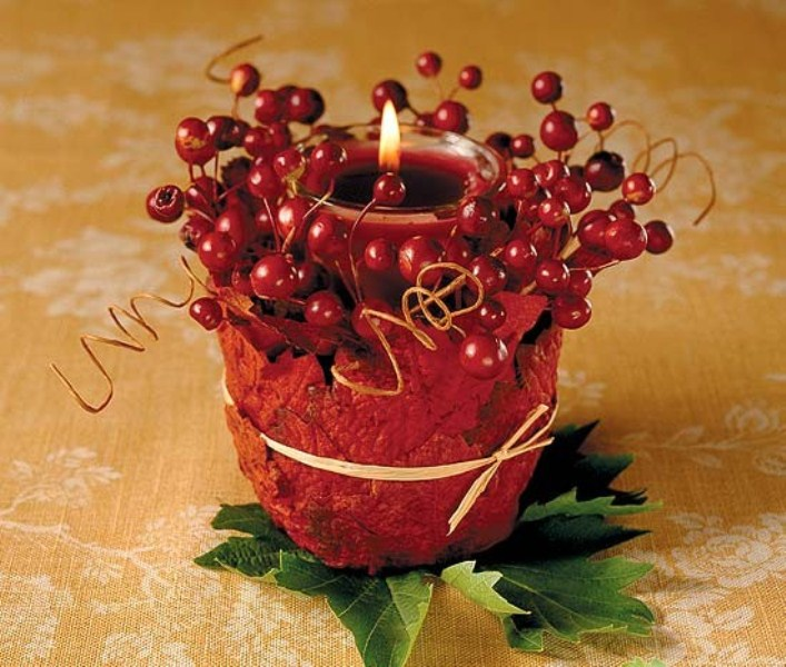 a cool fall wedding decoration of a glass candleholder with a red candle covered with faux leaves and berries