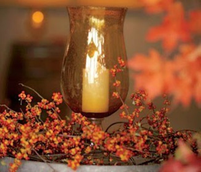 a candle lantern surrounded with berry branches and vines is a lovely fall centerpiece or decoration