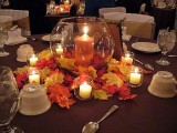 a fall wedding centerpiece of an aquarium with a candle, bright faux leaves and several candles is easy to compose