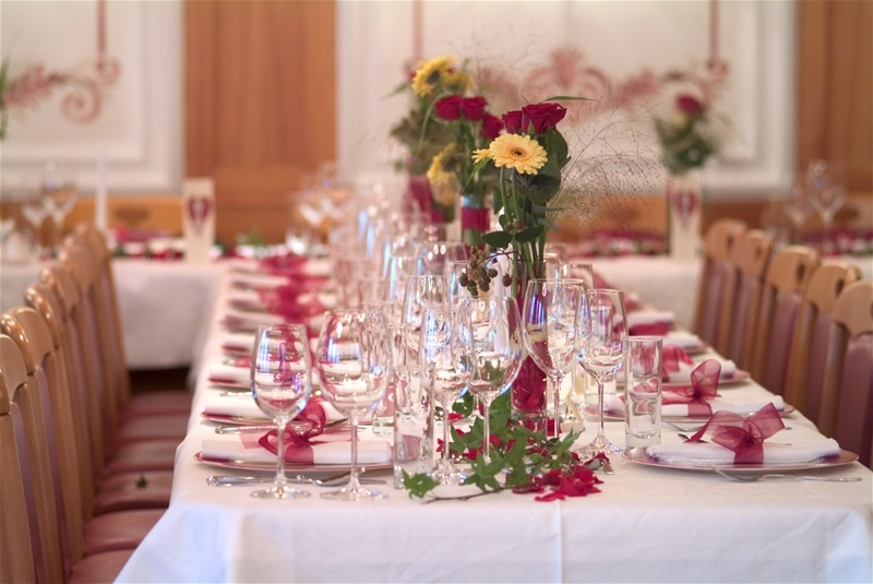 bright fall floral arrangements in vases and touches of burgundy accessorize wedding reception tables and make them feel like fall