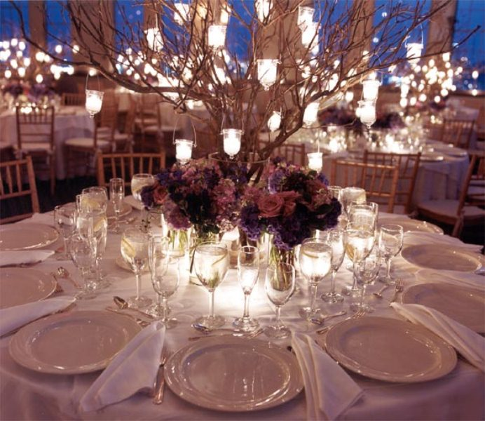 a refined fall wedding centerpiece of dark blooms, candles and branches with candleholders hanging on them