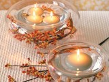 glass bowls wrapped with vine and berries and with floating candles will bring a cozy feel to your reception