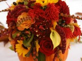 a pumpkin with bright and colorful fall blooms and leaves is a bold fall decoration or centerpiece