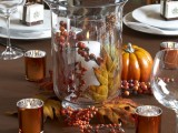 a fall wedding centerpiece of a tall glass vase with a candle, berries and a leaf and candles around it