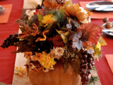 a natural fall wedding centerpiece of a pumpkin with bold leaves, blooms and berries cascading down looks lush and chic