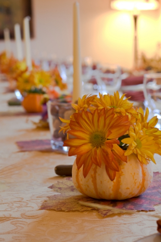 a pumpkin with bright blooms and candles in glasses for decorating the wedding reception table