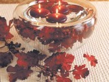 a glass bowl with bright leaves and berries and burgundy floating candles for decorating a wedding space