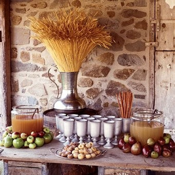 a fall wedding drink station with apple cider tanks placed on apples and a wheat bundle in a large vintage urn