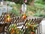 pumpkins and bright blooms and greenery in pumpkins decorate the wedding aisle in a cool rustic way